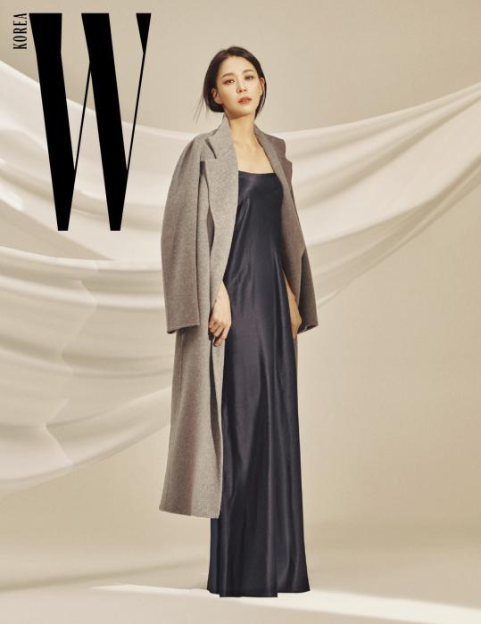 가늘고 긴 실루엣을 연출하는 회색 캐시미어 100% 테일러드 코트와 네이비 색상 실크 슬립 드레스는 Demoo 제품.