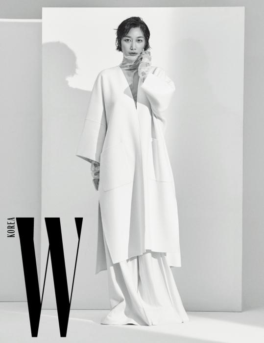 간결한 디자인이 돋보이는 흰색 코트, 메시 톱, 통넓은 팬츠는 모두 Demoo 제품.