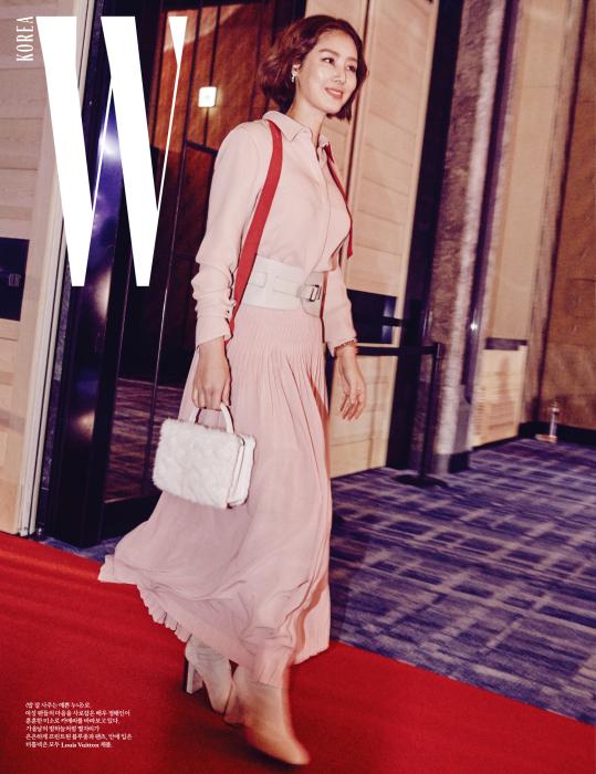 밝은 표정으로 입장하는 배우 김성령. 유방암 캠페인 컬러인 분홍색으로 사랑스럽게 연출했다. 허리에 벨트 장식이 있는 차분한 분홍색 드레스와 퍼 장식 백, 앵클 힐은 모두 Loro Piana 제품.
