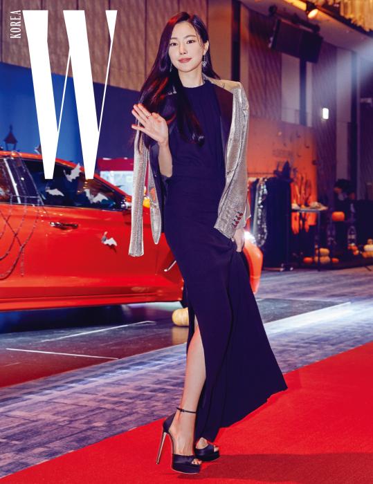 시크한 드레스 룩을 선보인 가수 손나은이 취재진을 향해 수줍게 인사하고 있다. 블랙 드레스와 어깨에 걸친 메탈릭한 턱시도 재킷은 Lanvin 제품.