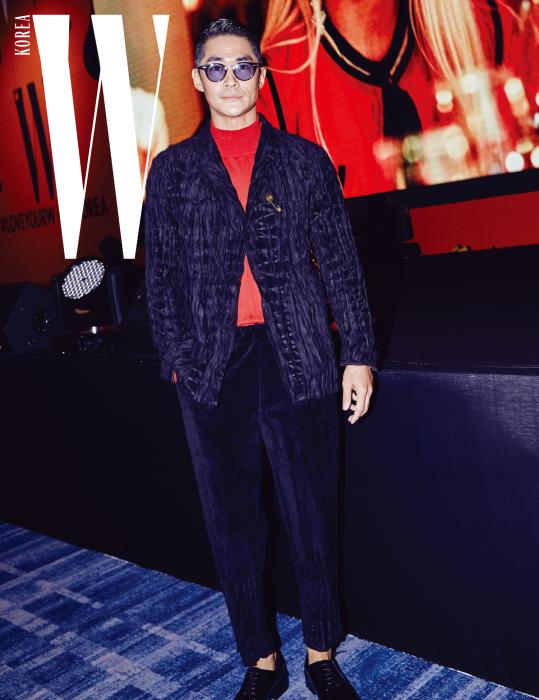 강렬한 패션으로 시선을 사로잡은 배우 배정남. 구겨진 듯 주름이 잡힌 검정 재킷과 팬츠, 안에 입은 빨간색 니트 톱은 모두 Issey Miyake Men 제품.