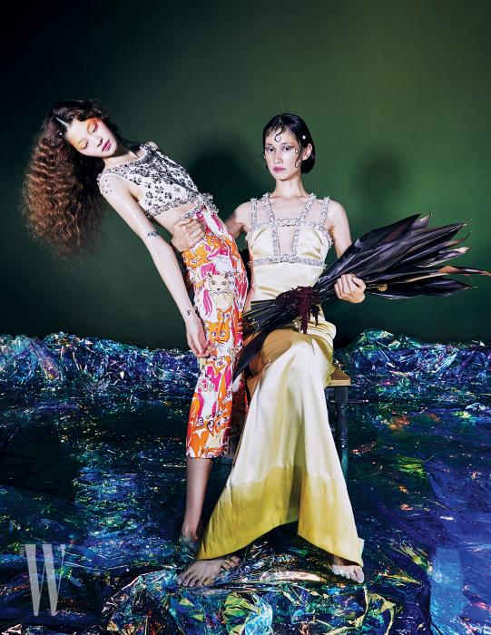 김아현이 착용한 화려한 비즈 장식의 애니멀 프린트 드레스는 Miu Miu 제품. 박세라가 착용한 파스텔 톤 롱 새틴 드레스는 Miu Miu 제품.