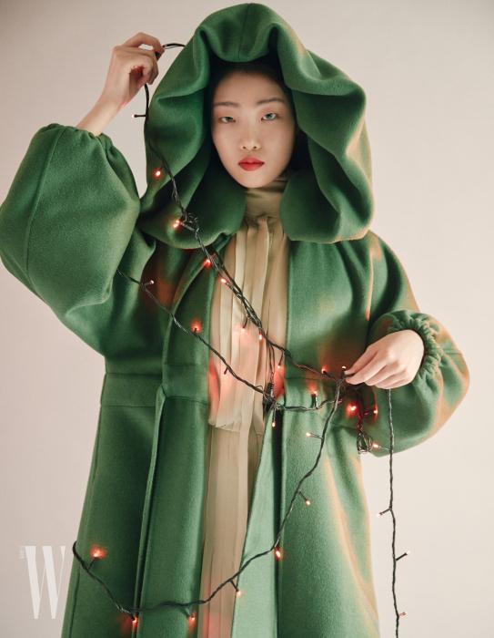 커다란 후디 코트, 주름 장식 드레스는 발렌티노 제품.