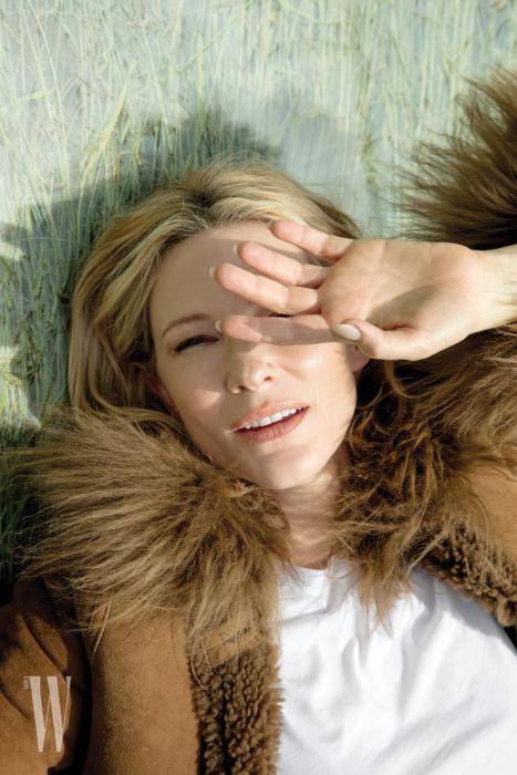털 장식의 갈색 코트는 Sonia Rykiel, 흰색 티셔츠는 Vince 제품.
