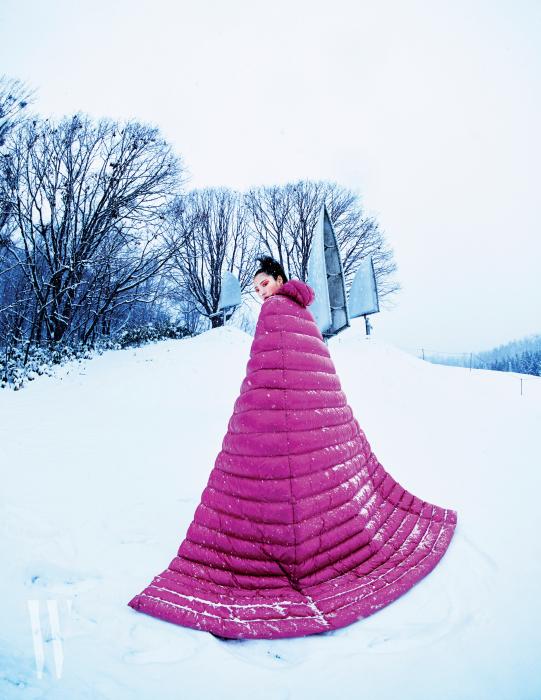 드라마틱한 실루엣의 핑크색 롱 패딩은 1 Mocler Pierpaolo Piccioli 제품. Susumu Shingu의 작품 'Meadow of Clouds'.