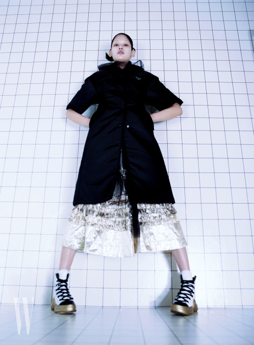 검정 나일론 패딩 재킷, 샤 소재 블라우스는 프라다 제품. 가격 미정. 프릴 장식 금색 스커트는 몰리 고다드 by 한스타일 제품. 1백40만원. 아치라이트 레이스업 스니커즈는 루이 비통 제품. 1백만원대.