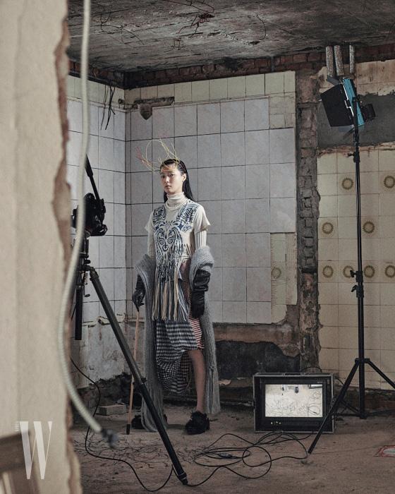 아이보리색 터틀넥은 Gucci, 프린지 장식 톱과 볼륨감 있는 헴라인이 특징인 스커트는 Loewe, 팔에 걸친 니트 숄은 Poiret by Boon the Shop, 가죽 장갑은 Cos, 신발은 4 Moncler Simone Rocha, 와이어 헤드피스는 Q millinery 제품.