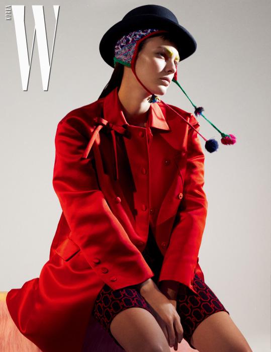 보 장식의 붉은색 새틴 코트와 그래픽 패턴의 자카드 팬츠는 Prada 제품. 겹쳐서 연출한 페루 모자는 스타일리스트 소장품.