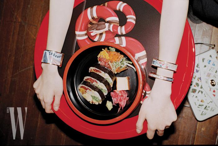 양손에 낀 꽃무늬 팔찌와 뱅글은 모두 에르메스 제품. 가격 미정. 강렬한 색감의 테이블과 바닥에 놓인 흰색 백은 구찌 제품. 테이블 1백98만원, 백 2백50만원.