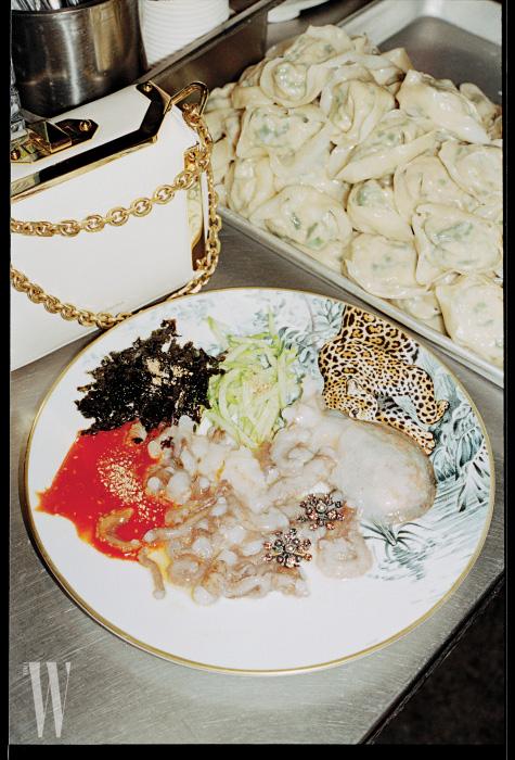흰색과 금색이 어우러진 미니 백은 알렉산더 매퀸 제품. 2백85만원. 산낙지 위에 올린 주얼 장식 귀고리는 보테가 베네타 제품. 66만5천원. 표범이 그려진 접시는 에르메스 제품. 가격 미정.
