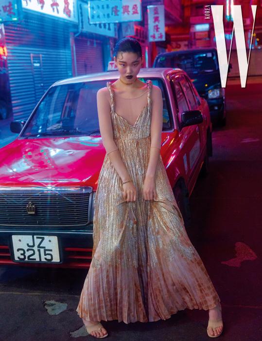 우아한 금색 롱 드레스와 안에 입은 타이츠, 샌들 힐, 금색 초커, 팔찌, 귀고리는 모두 Dior 제품.