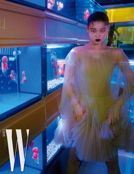발레복 스타일의 튤 드레스와 안에 입은 망사 보디슈트, 금색 초커, 투명한 볼 귀고리는 모두 Dior 제품.