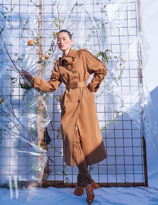 프릴 장식의 트렌치코트와 레그 워머는 Max Mara, 스트랩 샌들은 Salvatore Ferragamo 제품.