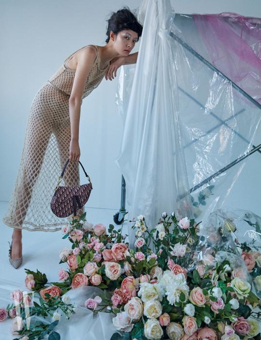 스킨 톤의 그물 장식 롱 드레스, 이너로 입은 브라와 브리프, 리본 장식 키튼힐 펌프스, 로고 패턴의 새들백은 모두 Dior 제품.